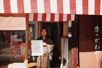 店の前にて、賞状を手に満面の笑顔の店主